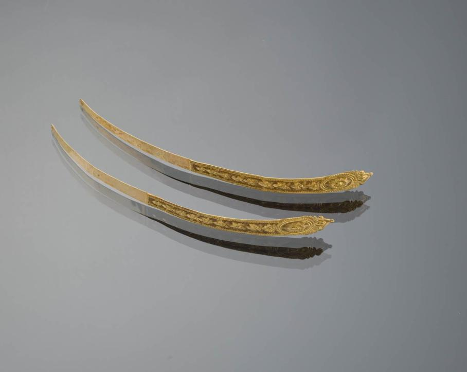'Zijnaalden'. These were worn as jewelry by pinning them into the cap, so they lay across the forehead. One was worn at a time. These are early 19th century in make.